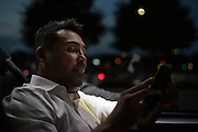 Oscar De La Hoya checks his phone on the ride back to the hotel at the end of the night in Grapevine, Texas on September 16, 2016.  (Cooper Neill for ESPN)
