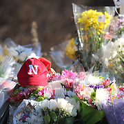 A baseball hat amongst the flowers at he shrine under the school sign in Sandy Hook after yesterday's shootings at Sandy Hook Elementary School, Newtown, Connecticut, USA. 15th December 2012. Photo Tim Clayton