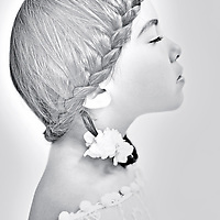 Close up of young girl with plaited hair wearing white lace dress in profile