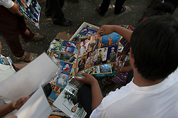 © Licensed to London News Pictures. 01/02/2013. Location, Cambodia. Street venders sell images of  the Late former King Norodom Sihanouk to mourners. Thousands of mourners lined the streets of Phnom Penh as part of the late kings royal funeral procession ahead of his Feb. 4, cremation Friday, Feb. 1, 2013, in Phnom Penh, Cambodia.  Photo credit : Charles Fox/LNP