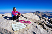 Climber on the summit of Mount Whitney with plaque in foreground (highest point in the continental US), Inyo National Forest, Sequoia National Park, California