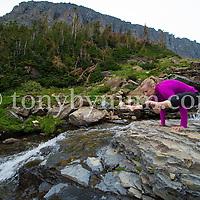 woman doing yoga hand balance on rock near mountain waterfall