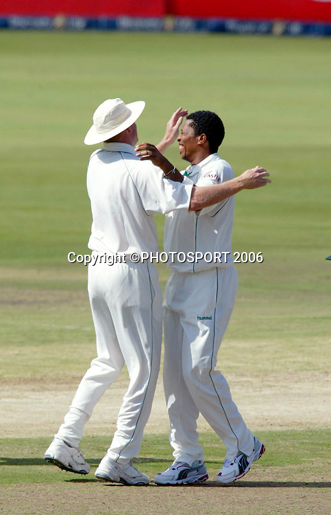 South Africa's Shaun Pollock and Makhaya Ntini celebrate taking a wicket on day two of the first cricket test between South Africa and New Zealand at SuperSport Park, Centurion, South Africa on Sunday 16 April, 2006. Photo: Africa Visuals/PHOTOSPORT**NZ USE ONLY**<br /> <br /> 160406 2 celebration celebrating