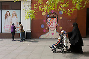 A Muslim mother and children walk past new mural of iconic musician and singer David Bowie has appeared on the wall of Morleys department store in Brixton, Lambeth, south London. The Bowie face is sourced (by artist James Cochran, aka Jimmy C) from the cover of Bowie's 1973 album Aladdin Sane at the height of his 1970s fame. The pop icon lived at 40 Stansfield Road, Brixton, from his birth in 1947 until 1953. This cover appeared in Rolling Stone's list of the 500 greatest albums of all time, making #277.