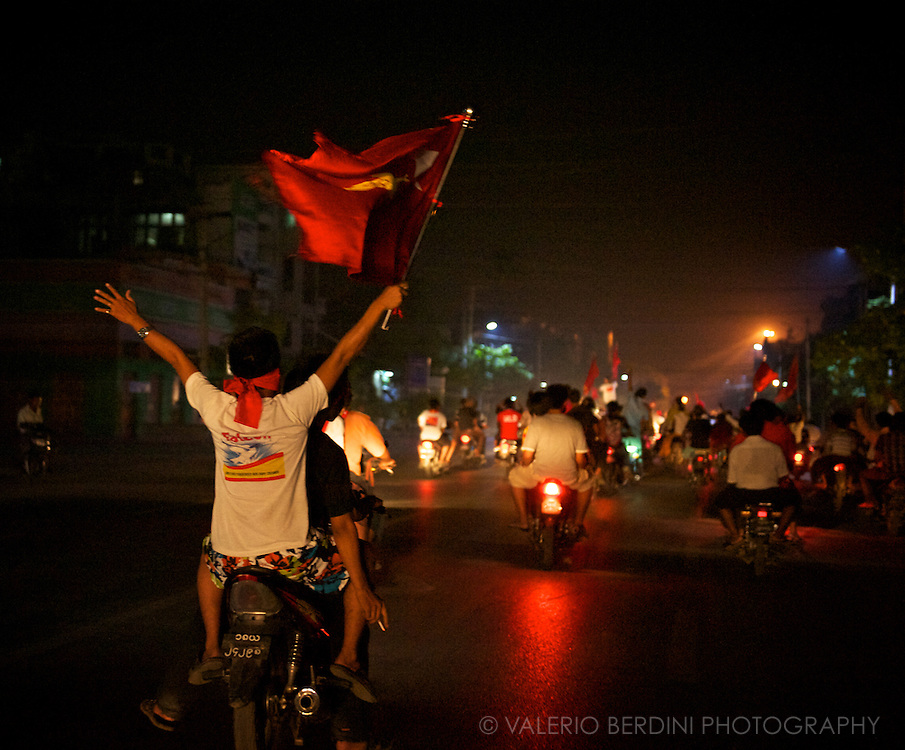 The NLD supporters' excitement is palpable. The parade gathers more and more vehicles as it passes by. Mandalay, Myanmar. 2012