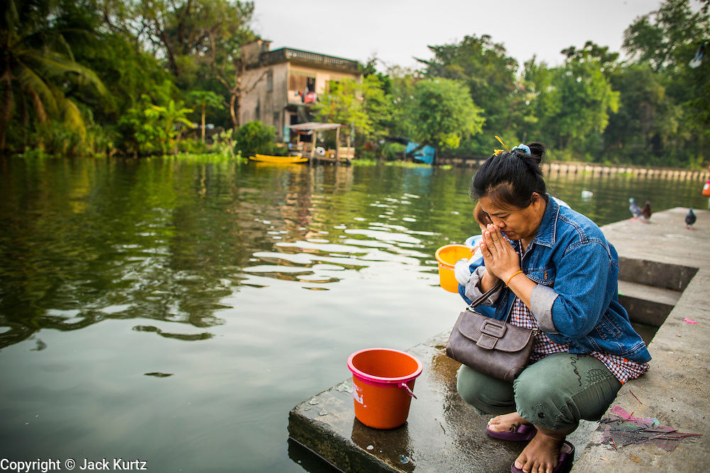 04 JANUARY 2012 - BANGKOK, THAILAND:  A woman prays before releasing fish into Khlong Phra Khanong to make merit at Wat Mahabut in eastern Bangkok. The temple was built in 1762 and predates the founding of the city of Bangkok. Just a few minutes from downtown Bangkok, the neighborhoods around Wat Mahabut are interlaced with canals and still resemble the Bangkok of 60 years ago. Wat Mahabut is a large temple off Sukhumvit Soi 77. The temple is the site of many shrines to Thai ghosts. Many fortune tellers also work on the temple's grounds.   PHOTO BY JACK KURTZ