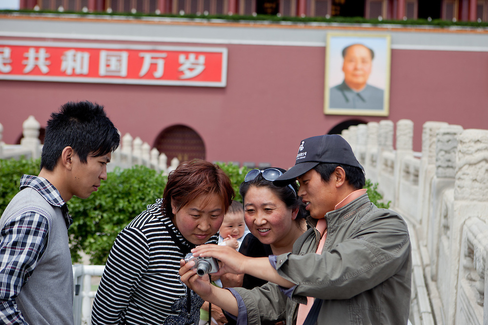 "A family is checking their digital photograph which had been made moments before at the main gate of ""The Forbidden City"" which was the Chinese imperial palace from the Ming Dynasty to the end of the Qing Dynasty. It is located in the middle of Beijing, China. Beijing is the capital of the People's Republic of China and one of the most populous cities in the world with a population of 19,612,368 as of 2010."