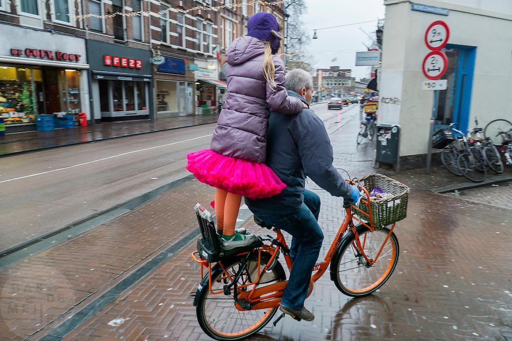 Fietser met meisje staand achterop de fiets door de regen van de Nobelstraat naar de Nobeldwarsstraat Utrecht.