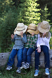 three children covering their faces with cowboy hats in Montana