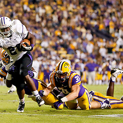 Oct 26, 2013; Baton Rouge, LA, USA; Furman Paladins running back Hank McCloud (26) is tackled by LSU Tigers linebacker Kwon Alexander (25) and linebacker D.J. Welter (31) during the first half of a game at Tiger Stadium. Mandatory Credit: Derick E. Hingle-USA TODAY Sports