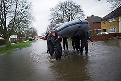 © London News Pictures. 12/02/2014. Egham, UK.  Members of the British Army Royal Engineers evacuating residents from their homes in Egham, Surrey, which has been hit by heavy flooding. Torrential  rain in the area is due to raise water levels increasing the risk of further flooding. Photo credit : Ben Cawthra/LNP