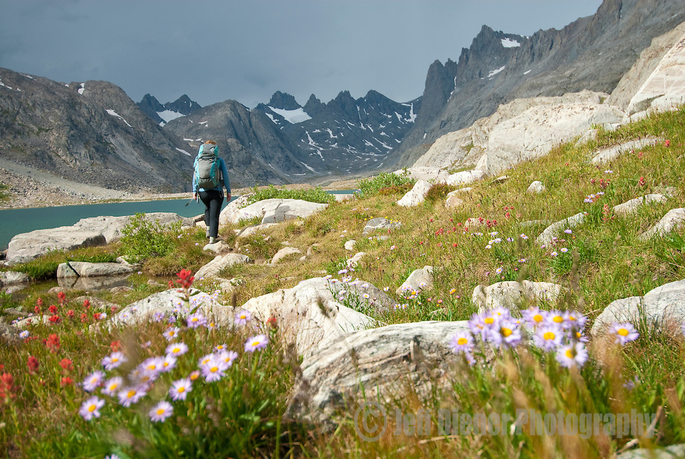 A young woman hikes through Titcomb Basin in the Wind River Mountains of  Wyoming.