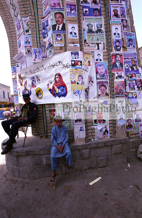 An Afghan police officer and a boy seat next to the arch in Kandahar. Posters, picturing political candidates to the Afghan parliamentary and local councils elections, are attached to the arch.
