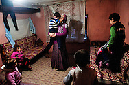 "Selcan Kesman holds her distraught son, surrounded by her children and several nieces and nephews.  Kesman shares the the tiny squatter dwelling with 3 families, 18 people in total.  Despite living in Istanbul for over ten years, the families say they are discriminated against for being Kurdish.  Feeling alone and isolated, she and her two sister-in-laws often confine themselves to the small ramshackle community they live in. The women say they feel as though integration is much harder for them than their husbands. ""We can't even ask our neighbors to watch our kids,"" said her sister in-law, Gulcan Kesman.<br />