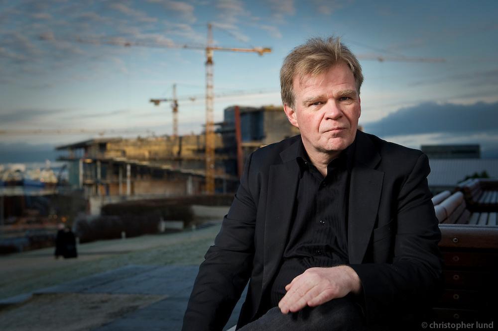 "Einar Már Guðmundsson, rithöfundur. í baksýn er tónlistarhúsið Harpa. Einar Mar Gudmunsson, writer. In background is the The Icelandic National Concert and Conference Centre ""Harpa"" under construction."