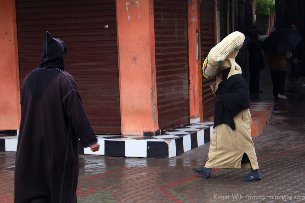 Africa, Morocco, Marrakech. Locals of Marrakech walking in rain.