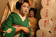 """'Kosen',(in green, a 20 year old Maiko girl) whose name means """"little fan"""",  with 'Yachiho' (in gold, a geisha girl) at the entrance to the tea-house in the 'Kaden' tea house in the Geisha district of Miyagawacho, Kyoto. The fans bear the names of various Geisha girls."""