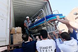 Men load medical equipment into a shipping container that has been donated to humanitarian agency Hand In Hand for Syria (HIHS). Equipment will then be delivered to some of the 56 field hospitals inside Syria that HIHS supplies.