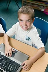 School boy using computer in classroom smiling,