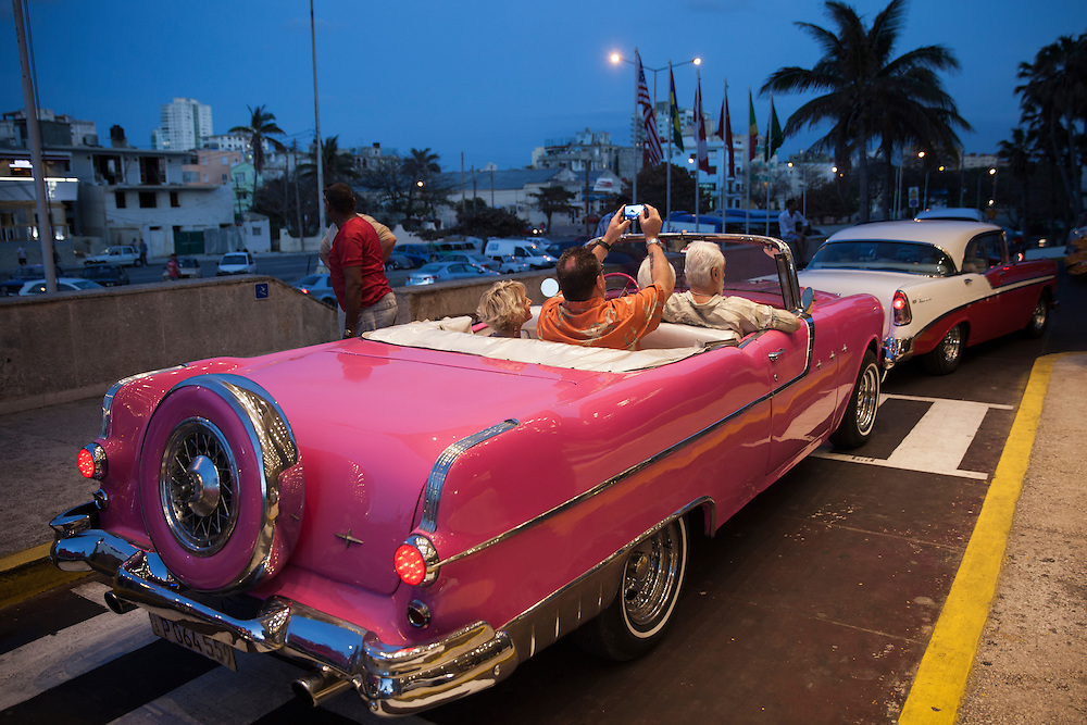 Tourists take selfies while enjoying a night ride on one of the traditional old American convertibles in Havana, Cuba.