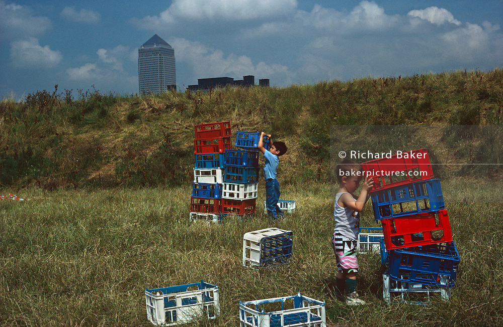 Two young boys concentrate on piling plastic bottle crates on top of each other making towers that echo the tall Canary Wharf tower structure a mile away in the background at Dockland's area of East London. On the grassy bank at Mudchute, a city farm on London's Isle of Dogs, the pile of crates is untidy and unstable making them lean at odd angles making the boys hold on to their building projects. They are dressed for a summer afternoon's activity in a seemingly rural location but which is, in fact, an area of inner-city London.