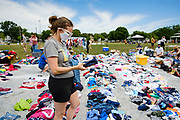"""19 JULY 2020 - DES MOINES, IOWA: Volunteer ALLISON PETERSEN sorts donated clothing before """"A Celebration of Black Motherhood"""" in Des Moines Sunday. The event was organized by the Supply Hive and Black Lives Matter. Items were donated by members of the community and redistributed to at risk families. They distributed diapers, sanitary products, clothes, books, and toys. They had enough material to help 200 families.        PHOTO BY JACK KURTZ"""