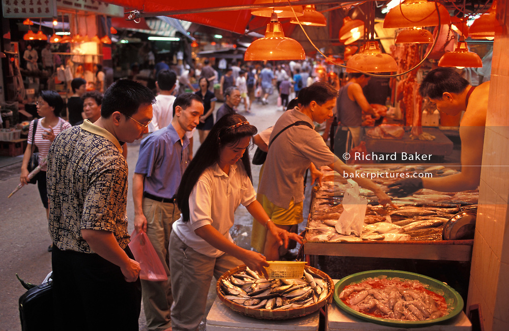 Hong Kong Chinese shop for fresh fish from a stall in a street market in Mid-Levels, on the eve of the handover of sovereignty from Britain to China, on 30th June 1997, in Hong Kong, China.  Midnight signified the end of British rule, and the transfer of legal and financial authority back to China. Hong Kong was once known as 'fragrant harbour' (or Heung Keung) because of the smell of transported sandal wood.
