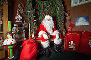 A comical feature showing the diverse and wide variety of Santa Clause's one can find in and around London. Father Christmas seems to have a wide range of appearances and different types of grottos from the elaborate Hamley's Toy Store to a garden shed in a Chobham garden centre. <br /> Pictured - Santa Clause and his grotto at Oak Tree Garden Centre, Ascot.<br /> Credit: Rick Findler / Story Picture Agency