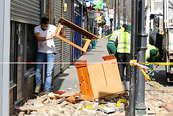© Licensed to London News Pictures. 10/03/2019. London, UK. A man from Stokey Vintage Cafe on Stoke Newington High Street collects his belongings after the roof collapsed this morning due to high winds. Photo credit: Dinendra Haria/LNP