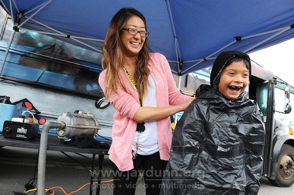 Alex Ocampo, 7, has fun getting vacuumed by second-grade teacher Jennifer Kuramura at a Physics Bus science demonstration at the Alisal Community School.