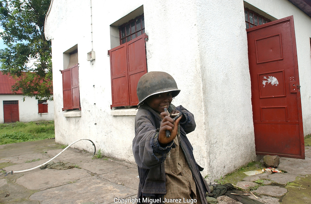 Rumangabo, DRC.-<br /> A young boy plays with a slingshot wearing an old military helmet in the abandoned military base of Rumangabo,   the second military base in the eastern Congo. (Photo by Miguel Ju&aacute;rez Lugo))
