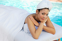 Young Chinese woman lying under towel by swimming pool, portrait