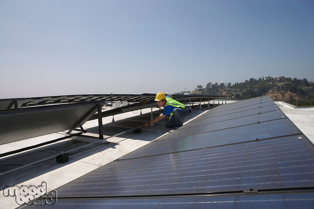 Maintenance worker checks solar array on rooftop in Los Angeles California