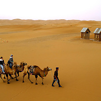 Chinese tourist ride camels at the exclusive Moon lake resort complex in to the Gobi desert, one of the bigger desert in the world,  far west of China, in the Inner Mongolia Autonomous Region. Aug-28-2006/ Photo: Stringer