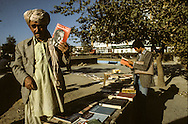 Afghanistan. the communist regime . the book of brejnev on sale in the bazar. / city life in the bazar,   kabul  Afghanistan  / Le regime communiste . les livres de brejnev sont vendus dans le bazar. scenes de rue dans le bazar  Kaboul  Afghanistan  / nb 26700 20/ AFG26700 20B