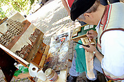 Amsterdam - Netherlands . A painter on the Prinsengracht in the centre of Amsterdam selling and painting traditiol paintings for tourists