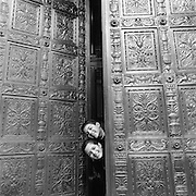 Boy and Girl peek out through doorway, black & white