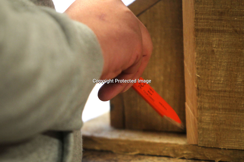 Bryce takes his pencil to make out the pattern he needs to cut for the base of his birdhouse.