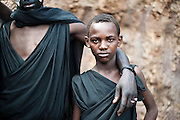 Two Maasai 'morani' who have recently undergone circumcision as a rite of passage, don black garments during a two week transition period before wearing the traditional clothes of a Maasai warrior.
