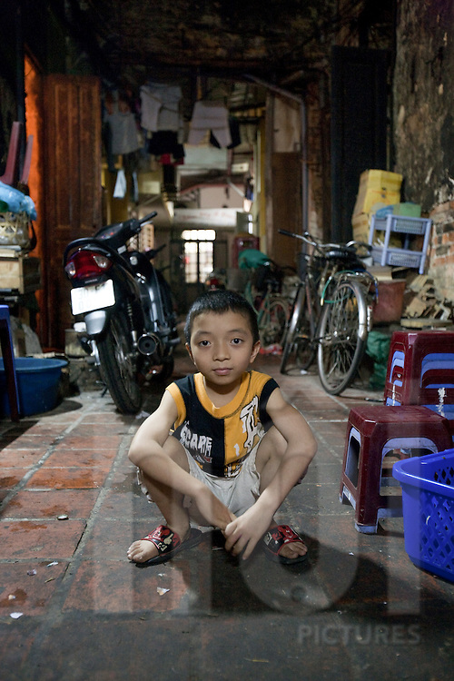 A young boy squats in his alley way while his parents run a night drink stall. Hanoi, Vietnam, Southeast Asia