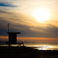 Photo of Newport Beach lifeguard tower 19 during sunrise on Balboa Peninsula beach in California.  Newport Beach is  located in Orange County in Southern California along the Pacific Ocean.