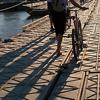 Walking bicycles across the pontoon bridge leading from Zemun to the Great War Island, Belgrade, Serbia.