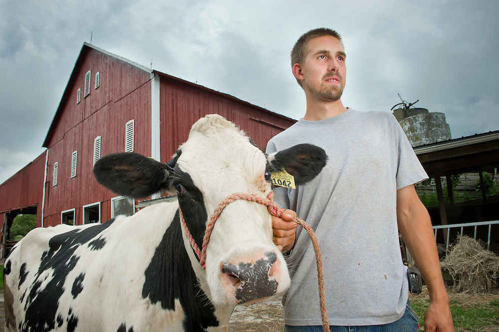 Man holding reigns of Holstein dairy cow while standing in front of a barn.