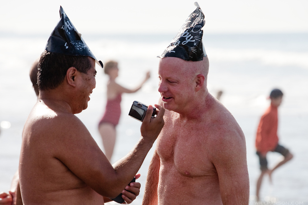 Randy Arnayro, a schoolteacher from Temecula, shows a photo on his camera to his husband Chuck Hartley during the Penguin Plunge in Del Mar on New Year's Day.