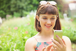 Close up of Teenage Girl Using Smartphone Outdoors, Smiling