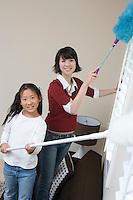 Woman and girl (10-12) doing housework