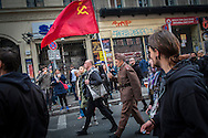 "01/05/2015 – Berlin, Germany: A man dressed as a Soviet soldierholding a flag of the USSR walks on the ""Myfest"" street festival. ""Myfest"" takes place in district SO 36, the traditional centre of riots that usually occur during May Day celebrations and it was organized to decreased the violence caused by Revolutionary May Day Demonstrations.  The radical left wing criticises such events claiming that it is pretended to pacify social conflicts and to ban radical demonstrations. The International Workers Day is a celebration of laborers and the working classes that is promoted by the international labor movement, anarchists, socialists, and communists and occurs every year on May Day. (Eduardo Leal)"