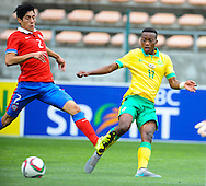 CAPE TOWN, SOUTH AFRICA - Sunday 27 September 2015: Khanyisa Mayo of South Africa kicks the ball past Simon Ramirez of Chile during the U17 International friendly soccer match between South Africa v Chile at Athlete Stadium. (Photo by Roger Sedres/ImageSA)