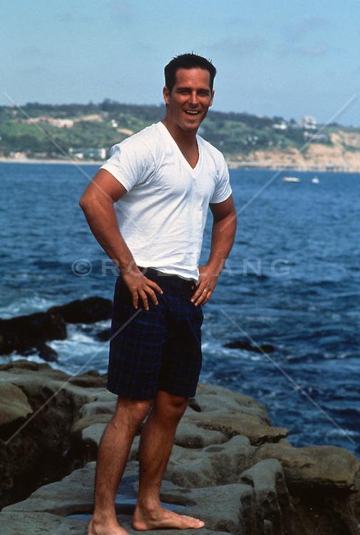 Man in white tee shirt enjoying time by the ocean