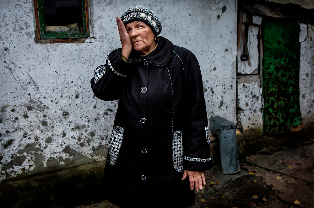 Luhanske, eastern Ukraine, Nov. 2017.<br /> <br /> Mariya Vasilyevna, 58.<br /> <br /> With her house in the background, pock marked by shrapnel, she describes the time when four artillery shells exploded on the property in 2015. Fired from pro-Russian separatists&rsquo; positions they destroyed the roof, all the windows and their car.<br /> <br /> Her son and his uncle heard the shellfire getting closer and managed to get a few steps into their cellar before the first one landed in the courtyard. Because of the increased intensity of the attacks she had already left and didn&rsquo;t return for 8 months.<br /> <br /> The roof was repaired through support from the UNHCR, but they still need new windows and will have to carry out repairs to these and the rest of the extensive damage themselves. <br /> <br /> As this is a military town the situation is still dangerous and only a few of her neighbours have returned home.  <br /> <br /> She owns a cow and survives by selling milk to the local market to support herself and her father, who lives with her.